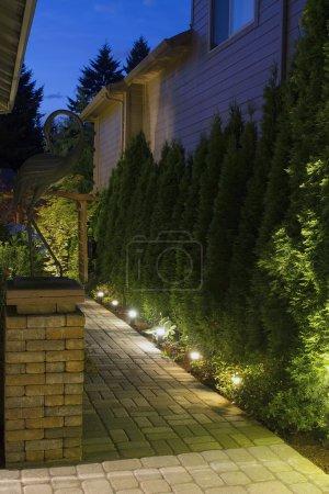 Photo pour Colonne de brique de chemin de pavés de jardin d'arrière-cour avec la grue en bronze la nuit - image libre de droit