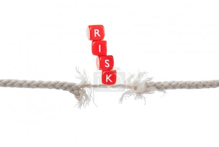 Photo for Dice labelled risk balanced on breaking rope - Royalty Free Image