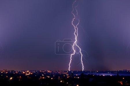 Удар молнии над темно-голубым небом в ночном городе