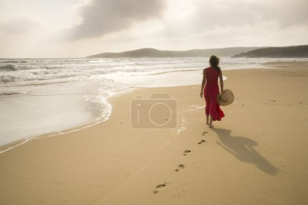 Photo for Young woman walk on an empty wild beach towards celestial beams of light falling from the sky - Royalty Free Image