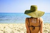 žena na pláži symbolem slunce na zádech