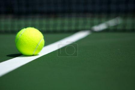Photo pour Balle de tennis sur le court avec le net en arrière-plan - image libre de droit