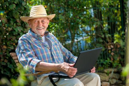 Photo for Elderly man using laptop in the park - Royalty Free Image