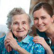 Senior woman with her caregiver at home...