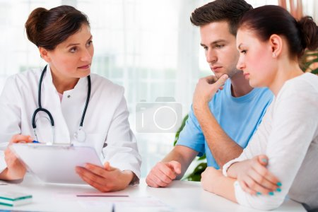 Photo for Doctor woman offering medical advices to a young couple in office - Royalty Free Image