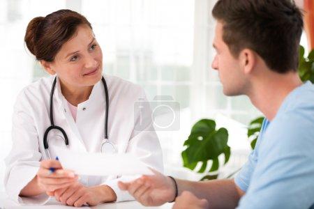 Photo pour Médecin parlant à son patient de sexe masculin au bureau - image libre de droit
