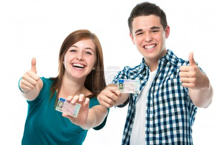 Happy teens showing their driving license...
