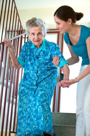 Photo for Senior woman is climbing stairs with caregiver - Royalty Free Image