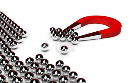 Red horseshoe magnet attracting some chrome balls from a crowd, white background