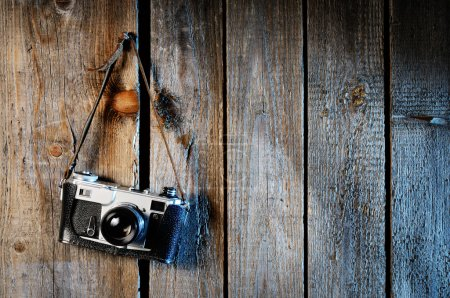 Old camera on weathered wooden background...