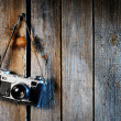 Old camera on weathered wooden background