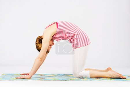 Beautiful woman doing cat yoga pose