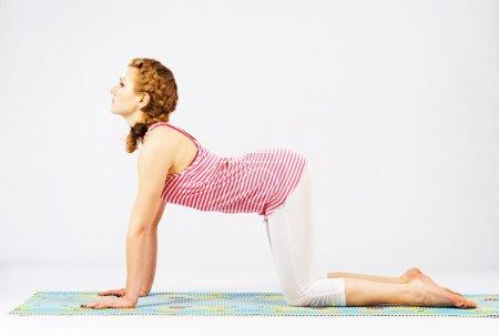 Beautiful woman doing cow yoga pose.