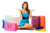 Beautiful cheerful woman sitting among shopping bags