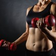Fitness woman training with red dumbbells, closeup...