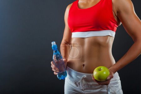 Photo for Torso of a woman with a bottle of water and green apple on a dark background - Royalty Free Image