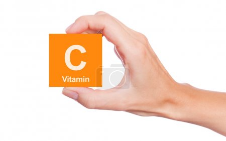 Hand that holds a box of vitamin C isolated on whi...