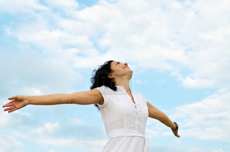 Photo for Happy smiling woman standing with outspread arms and her face lifted to the cloudy blue sky - Royalty Free Image