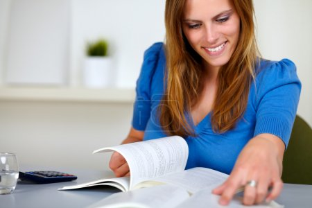 Lovely blonde girl smiling and reading