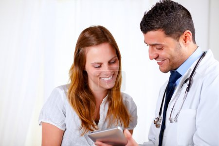 Latin doctor and a patient looking to tablet PC