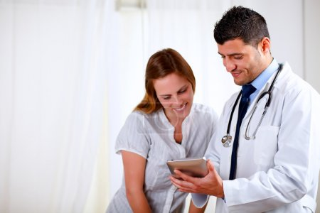 Handsome doctor and a woman looking to tablet PC