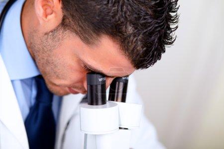 Photo pour Closeup portrait d'un homme médical professionnel à l'aide d'un microscope - image libre de droit