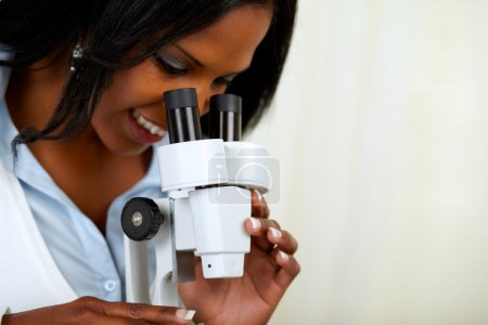 Beautiful american black woman with a microscope