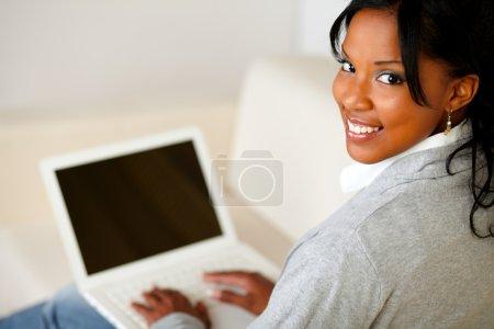 Photo pour Portrait d'une belle jeune femme travaillant sur ordinateur portable tout en se tourne vers vous - image libre de droit