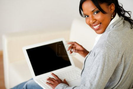 Photo for Portrait of a beautiful black female working on laptop on sofa at home while is looking to you - Royalty Free Image