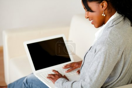 Photo for Portrait of a relaxed afro-American woman browse the Internet on laptop while is sitting on sofa at home indoor - Royalty Free Image