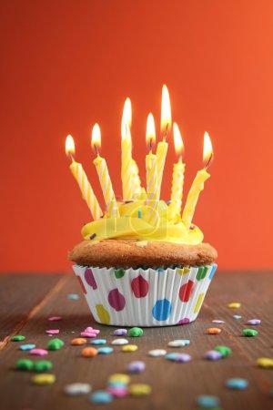 Photo pour Cupcake avec glaçage jaune plein de bougies jaunes sur fond orange - image libre de droit