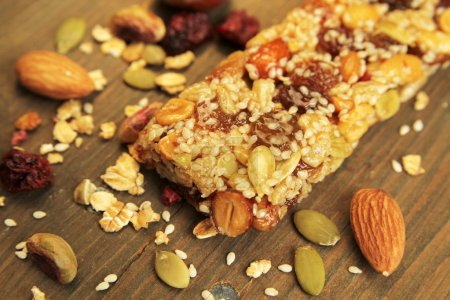 Photo for Organic granola bar with nuts and dry fruits on a wooden table - Royalty Free Image