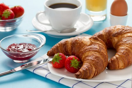 Photo for Breakfast with two croissants, strawberry, egg, orange juice and coffee - Royalty Free Image