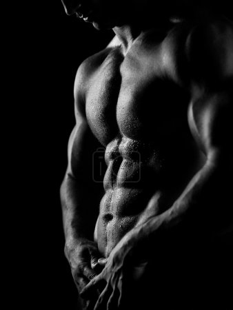 Photo for Black and white studio shoot of strong athletic man on dark background - Royalty Free Image