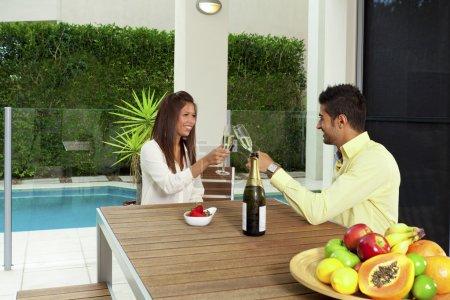 Photo pour Jeune couple toastant au champagne dans une cour moderne - image libre de droit