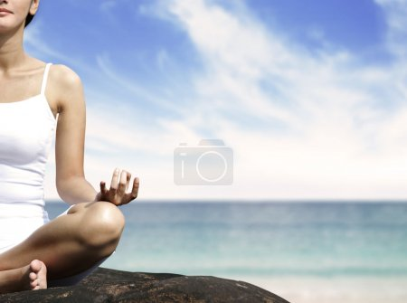 Woman meditating on a rock