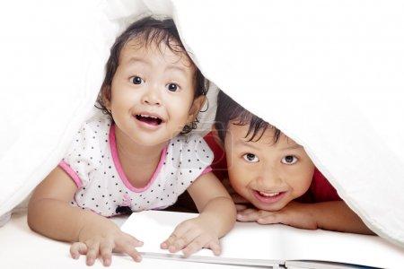 Cute siblings under blanket