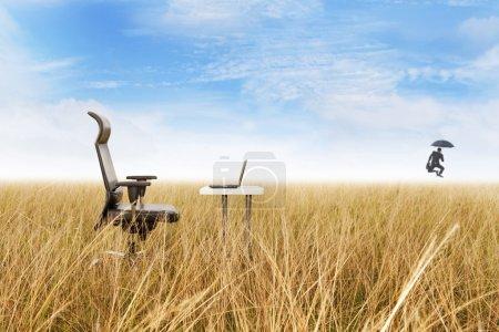 Foto de Oficina al aire libre en una hierba dorada con éxito hombre de negocios saltando dejando su oficina remota - Imagen libre de derechos