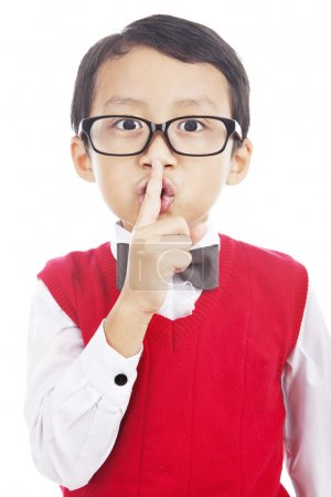 Photo pour Mignonne asiatique élève du primaire avec son doigt sur sa bouche, étouffer. - image libre de droit
