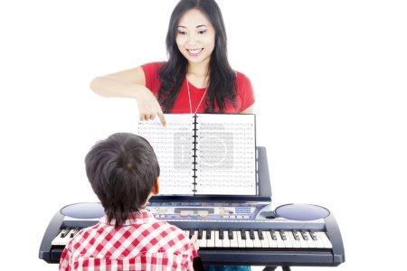 Photo pour Jeune garçon prenant des cours de piano à la maison avec son tuteur - image libre de droit