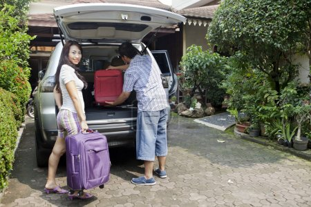 Photo for Smiling asian woman with her husband loading baggage in car, preparing for travel - Royalty Free Image