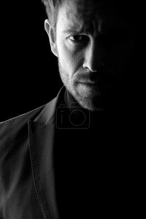 Photo pour Portrait de clé basse Studio en noir et blanc d'un âge moyen l'homme vêtu d'un blazer. - image libre de droit