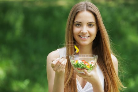 Photo for Close-up of happy beautiful young woman eating vegetable salad - Royalty Free Image