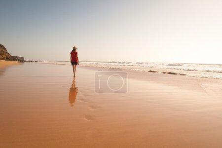Photo pour Lonely girl marchant dans une plage solitaire avec son reflet, au moment du coucher du soleil. heure d'été. - image libre de droit