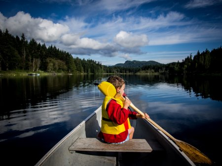 Child canoeing on lake...