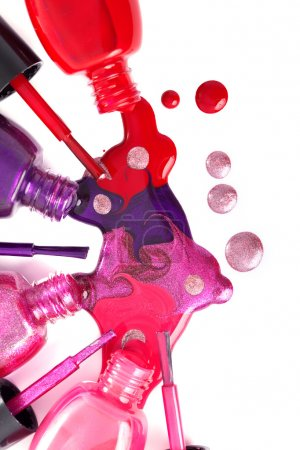 Ñolored nail polish spilling from bottles