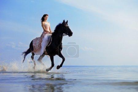 Photo pour Image d'une femme sur un cheval au bord de la mer - image libre de droit