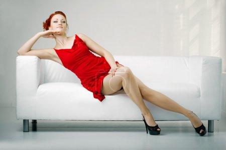 Photo pour Femme rousse luxueux dans une robe rouge sur canapé blanc - image libre de droit
