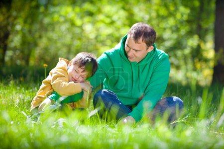 Foto de Lindo niño abraza a su padre en un día de verano en el parque - Imagen libre de derechos