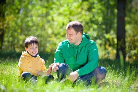 Foto de Padre de joven con su hijo en día de verano en el parque - Imagen libre de derechos